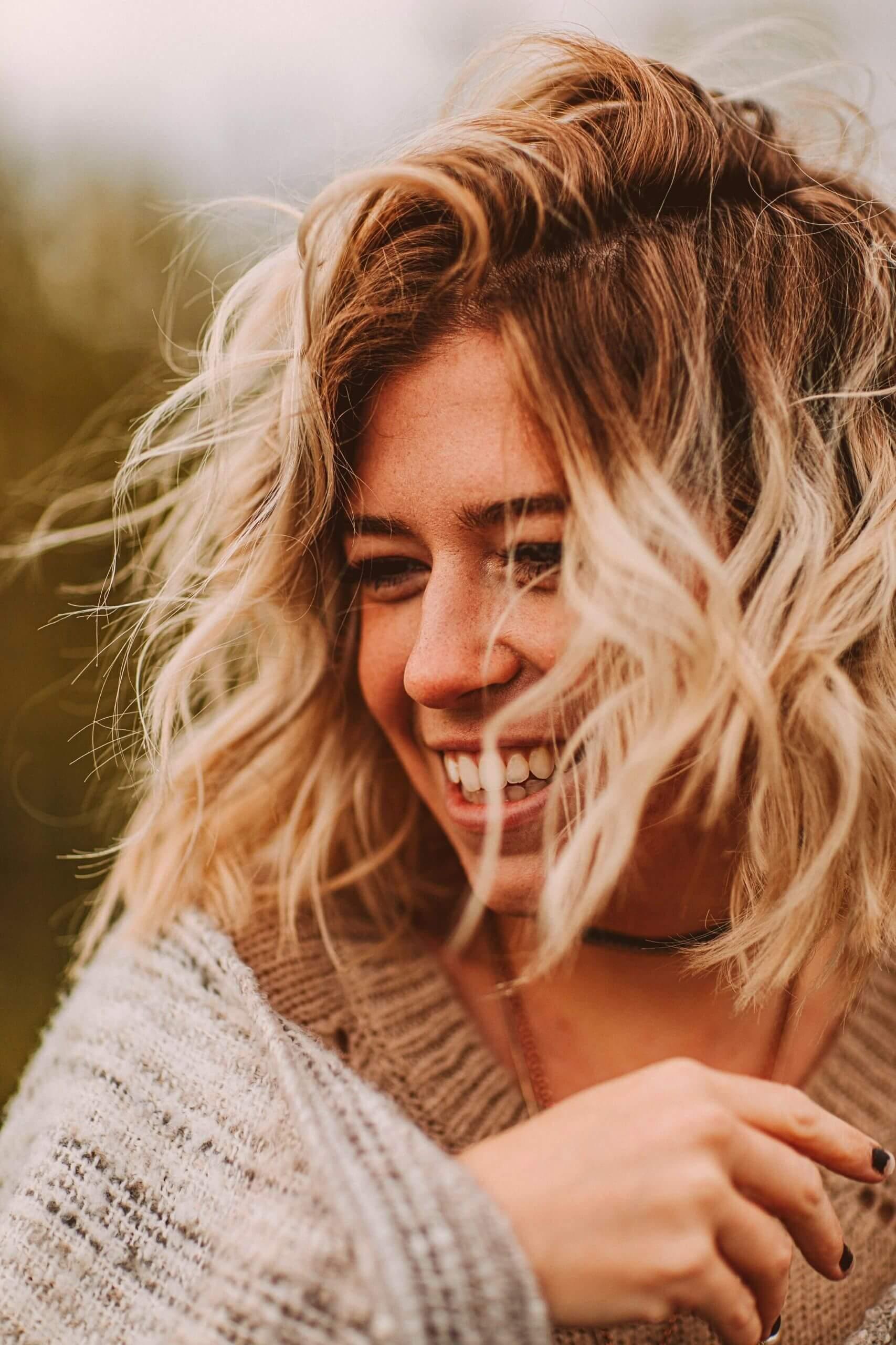 Lachende blonde Frau Portraetaufnahme vorne seitlich